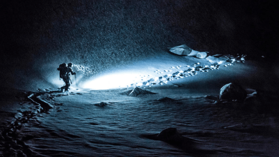 a hiker at night in the snow with a Lupine headlamp